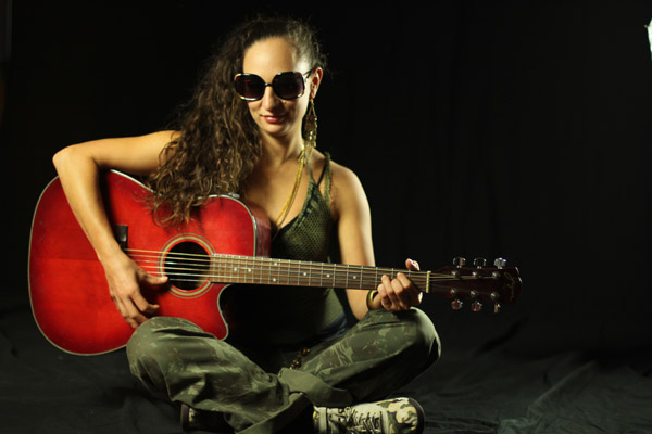 Auresia sitting with red guitar facing forward